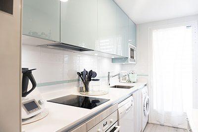 Cocina pequeña con tonos claros y espacio muy aprovechado
