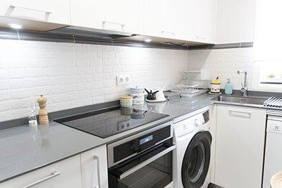 Cocina pequeña y blanca con gran capacidad de almacenaje