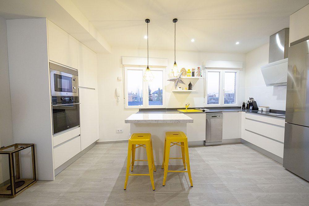 Cocina blanca y moderna abierta al salón, ¡con dos alturas de encimera!