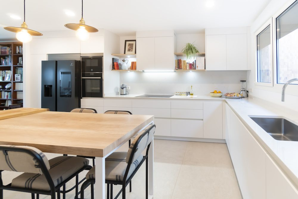 Cocina Blanca moderna con mesa y desayunador