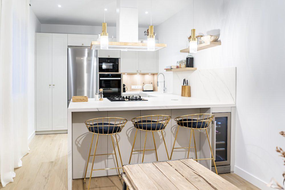 Cocina blanca abierta al salón con península y toques nórdicos