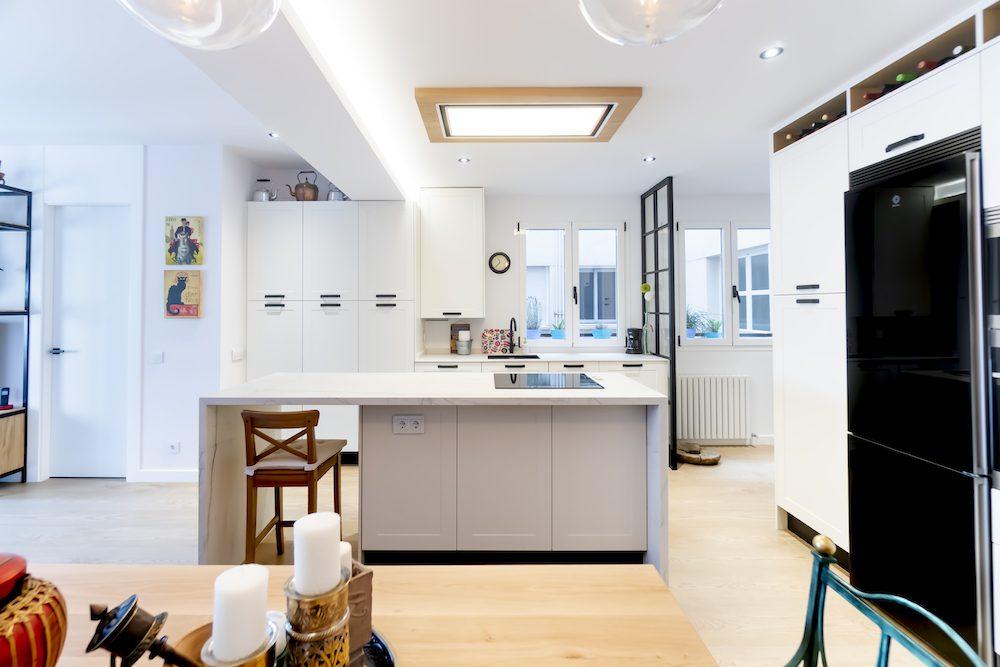 Cocina blanca integrada en el salón con isla