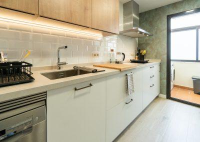 cocina blanca pequeña con madera y dos frentes